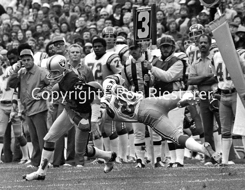 Oakland Raiders Fred Biletnikott spins away from San Diego Cornerback Mike Williams..(1975 photo/Ron Riesterer)