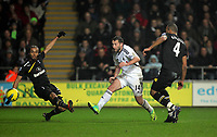 Pictured: Stephen Dobbie of Swansea (C) kicks the ball off target while closely marked by Benoit Assou-Ekotto (L) and Younes Kaboul of Tottenham Hotspur (R). Saturday 31 December 2011<br /> Re: Premier League football Swansea City FC v Tottenham Hotspur at the Liberty Stadium, south Wales.