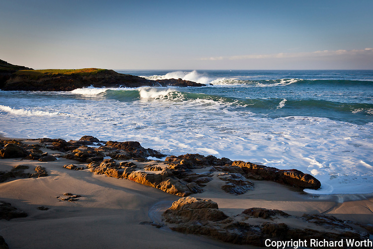 Waves roll onto the beach while morning light casts deep shadows among the rocks at Bean Hollow State Beach on California's coast.