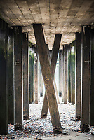 Underside of a pier on the banks of the River Thames, South Bank, London, England