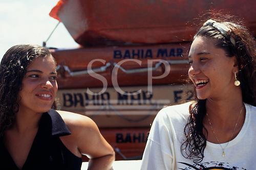 Salvador, Bahia, Brazil. Two smiling Bahiana girls with 'Bahia Mar' boats behind.