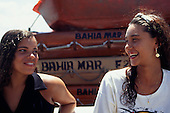 Salvador, Bahia, Brazil. Two smiling Bahiana girls with 'Bahia Mar' boats behind.