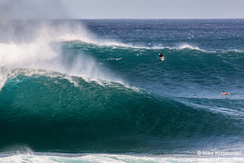 Surfers paddling over a big set at Pipeline, North Shore, Oahu