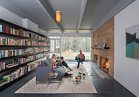 A family relax in a contemporary home library room with wall to wall book shelves. A comfortable grey upholstered sofa faces a fireplace with a lit fire.