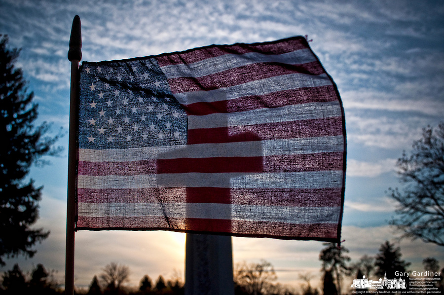An American flag, blown stiff in a heavy wind, sits in front of a large cross at sunset on Veterans Day in Blendon Cemetery on Hempstead Road.