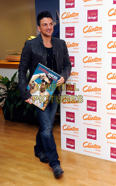 PETER ANDRE.signs copies of his new 2011 calendar at Clinton's Cards, Bluewater Shopping Centre, Kent, England, UK,.5th February 2011..full length jacket holding jeans necklace black leather waking .CAP/DH.©David Hitchens/Capital Pictures.