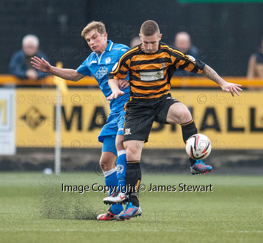 Queen of the South's Gavin Reilly and Alloa's Darryl Meggatt challenge for the ball.