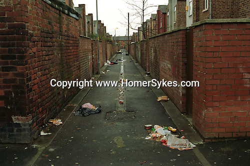 Rubbish strewn about in a back alley of terraced houses, Moss Side Near Manchester. England.