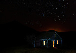 An abandoned home in Cascade County, Montana is lit from the interior with a flashlight after sunset with a large field of stars in the sky.