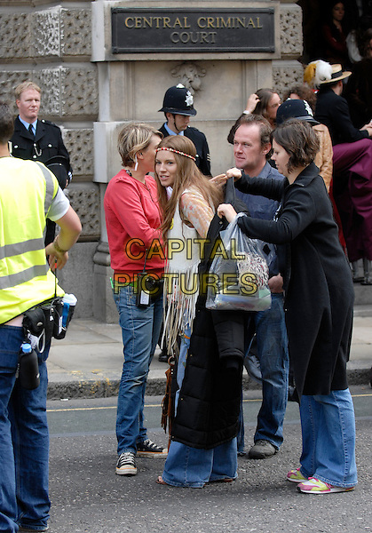 "SIENNA MILLER.On the set of her new film ""Hippie Hippie Shake"", outside The Old Bailey, London, England, September 16th 2007..full length film set filmset jeans  hairband head band cream fringed tassled waistcoat costume seventies style putting black coat on.CAP/IA.©Ian Allis/Capital Pictures"