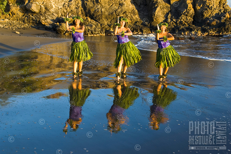 Three female hula dancers perform at the water's edge, their image is reflected in the wet sand near Lahaina.