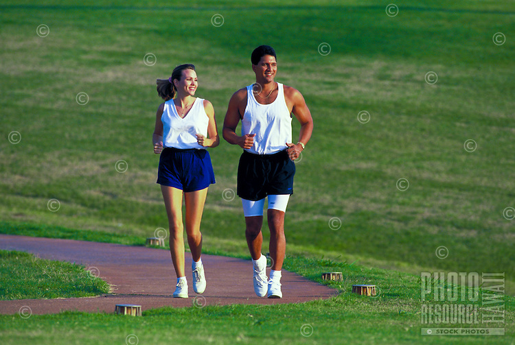A fit, young couple jog together on a path through a grass field.