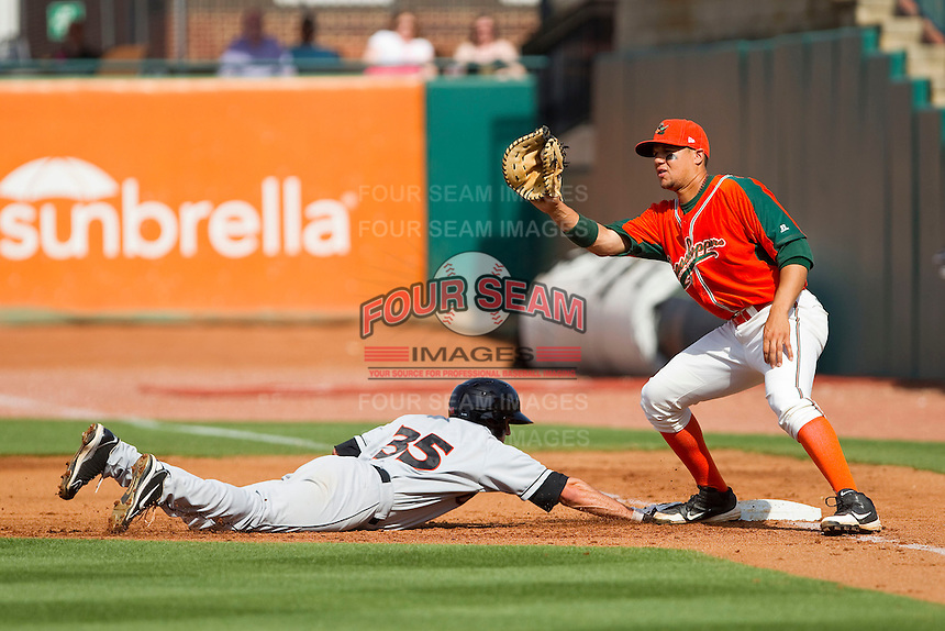 Viosergy Rosa (35) of the Greensboro Grasshoppers catches a pick-off throw as Lucas Herbst (35) of the Delmarva Shorebirds dives back to first base at NewBridge Bank Park on May 26, 2013 in Greensboro, North Carolina.  The Grasshoppers defeated the Shorebirds 11-2.  (Brian Westerholt/Four Seam Images)