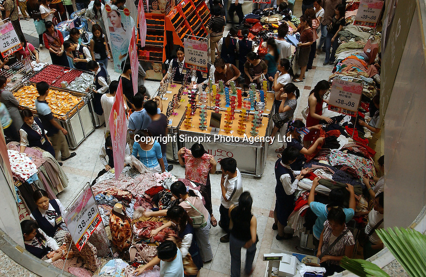 """Shoppers buy clothes and other items at a the Jusco department store in the Teem plaza in Guangzhou China during the May Day  """"golden week"""" holiday. A large domestic demand for all kinds of goods from China's emerging middle class is helping to drive China's booming economy..07 May 2005"""