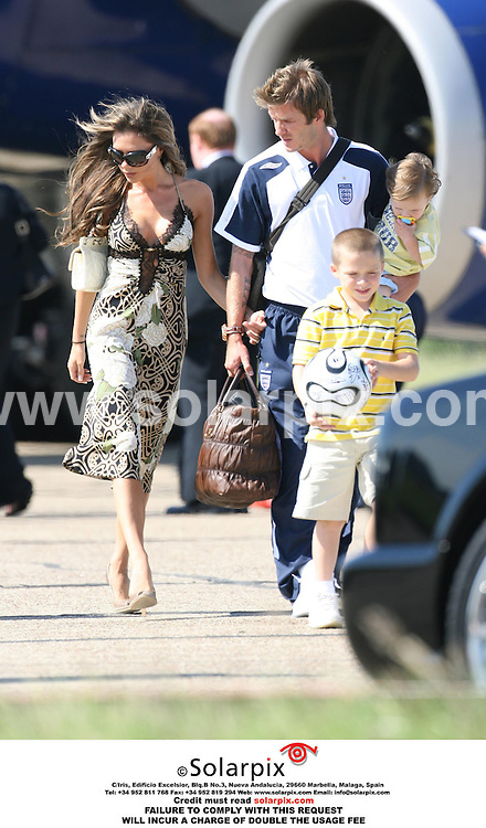 ALL ROUND PICTURES FROM SOLARPIX.COM..The England Team arrive at Stansted Airport on 02.07.06 after their exit from the 2006 World Cup. Job Ref: 2533/EBR..This pic: David, Victoria, Brooklyn, and Cruz Beckham..MUST CREDIT SOLARPIX.COM OR DOUBLE FEE WILL BE CHARGED..