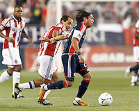 New England Revolution midfielder Lee Nguyen (24) dribbles at midfield as Chivas USA midfielder Nick LaBrocca (10) defends. In a Major League Soccer (MLS) match, the New England Revolution tied Chivas USA, 3-3, at Gillette Stadium on August 29, 2012.