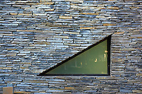 Detail of a small triangular window set in the slate wall