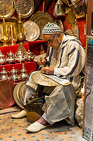 Fes, Morocco.  Metalworker Hammers a Design into a Tray.