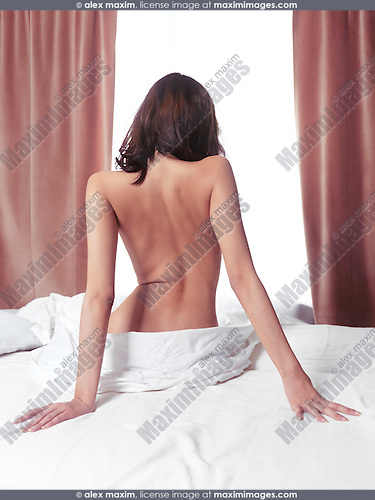Nude back of a young woman sitting on a bed in front of a brightly lit window