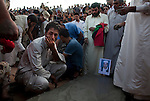 A man crouches next to the fresh grave of Ramadan Barghout, 70, during the burial of eight bodies found last week in a mass grave near the town of Al-Qala in the Nefusa Moutains, Libya, Friday, Sept. 30, 2011. The eight were reburied next to 35 bodies found in a separate mass grave in the area. Members of the Amazigh indigenous tribe, the men were arrested from their homes and at checkpoints by pro-Gaddafi forces, imprisoned, and finally executed sometime in June. The men, many of them related as fathers and sons, or as brothers, were missing until the first, larger mass grave was found in mid-August.