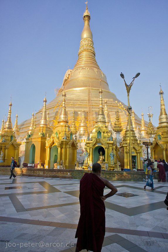 monk contemplates in front of Shwedagon pagoda complex, Yangon, Myanmar, 2011