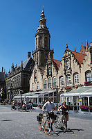 Belgium, West Vlaanderen, Veurne: Grote Markt with cyclists, restaurants and Saint Walburga`s Church tower (Saint Walburgakerk)