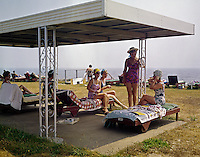 Women under an awning relaxing on lounge chairs at the Ocean Mist Motel in Bass River, Mass. 1960's
