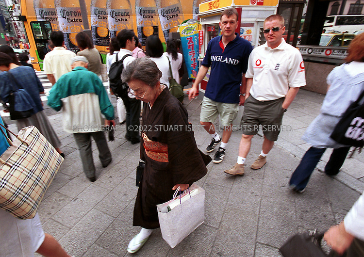 6/1/2002--Tokyo, Japan..Two England fans walking through Tokyo's exclusive Ginza district one day before England's opening match against Sweden on June 2nd in Saitama. Despite the huge influx of foreigners and 4 stadiums near Tokyo, the city has very few signs up for the World Cup series unlike Korea which has gone all out to welcome foreign guests...All photographs ©2003 Stuart Isett.All rights reserved.This image may not be reproduced without expressed written permission from Stuart Isett.