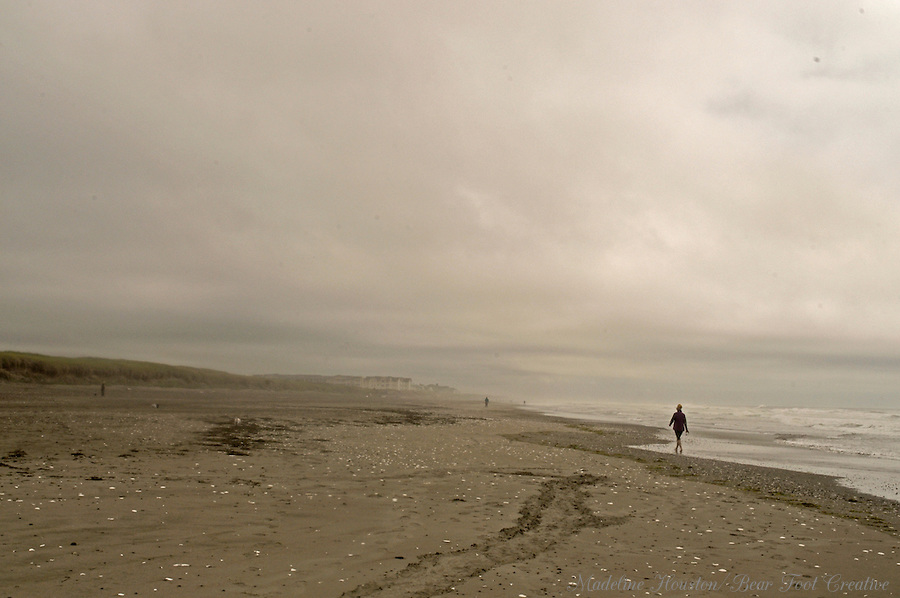 A woman walks along the beach in Westport State Park in Washington State, USA.