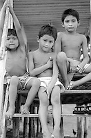 Three children sit on the steps of their home in the Amazonian town of Acajatuba, Brazil, which sits on the Rio Negro, March 5, 1999..