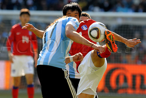 Ki Hun Yeom of South Korea fights for the ball with Jonas Gutierrez of Argentina during the FIFA World Cup 2010 soccer match between Argentina and South Korea at the Soccer City Stadium on June 17, 2010 in Johannesburg, South Africa.