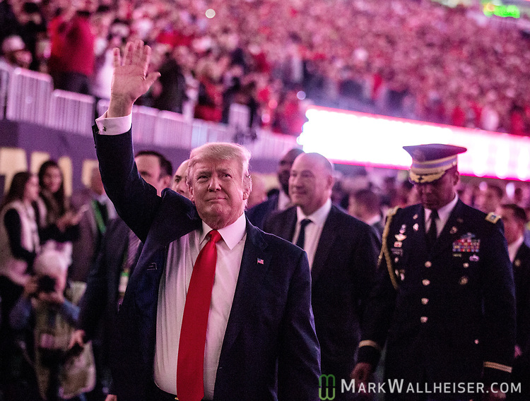 US President Donald Trump waves to the crowd after the National Anthem before the NCAA College Football Playoff National Championship at Mercedes-Benz Stadium on January 8, 2018 in Atlanta. Photo by Mark Wallheiser/UPI