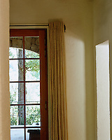 Curtains against the double French windows of the living room are classically simple