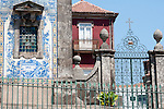 A tiled window of the Santo Ildefonson Church and the surrounding wall and gate, with a pink building in the background, in Porto, Portugal.