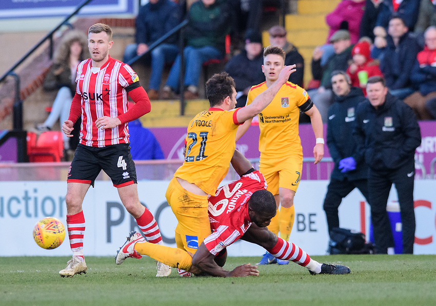 Lincoln City's John Akinde vies for possession with Northampton Town's John-Joe O'Toole<br /> <br /> Photographer Chris Vaughan/CameraSport<br /> <br /> The EFL Sky Bet League Two - Lincoln City v Northampton Town - Saturday 9th February 2019 - Sincil Bank - Lincoln<br /> <br /> World Copyright © 2019 CameraSport. All rights reserved. 43 Linden Ave. Countesthorpe. Leicester. England. LE8 5PG - Tel: +44 (0) 116 277 4147 - admin@camerasport.com - www.camerasport.com