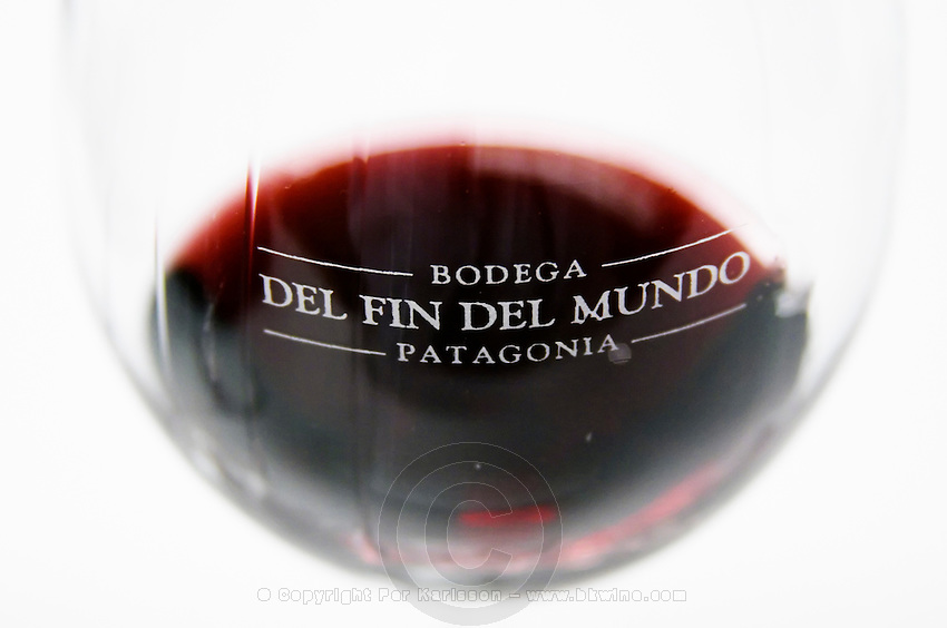 glass of red wine with engraved the name of the vineyard against a white background Bodega Del Fin Del Mundo - The End of the World - Neuquen, Patagonia, Argentina, South America
