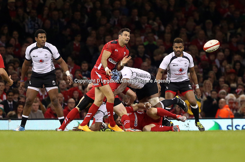 Pictured: Mike Phillips of Wales (2nd L) passing the ball while being tackled by Leone Nakarawa of Fiji. Saturday 15 November 2014<br /> Re: Dove Men Series rugby, Wales v Fiji at the Millennium Stadium, Cardiff, south Wales, UK.
