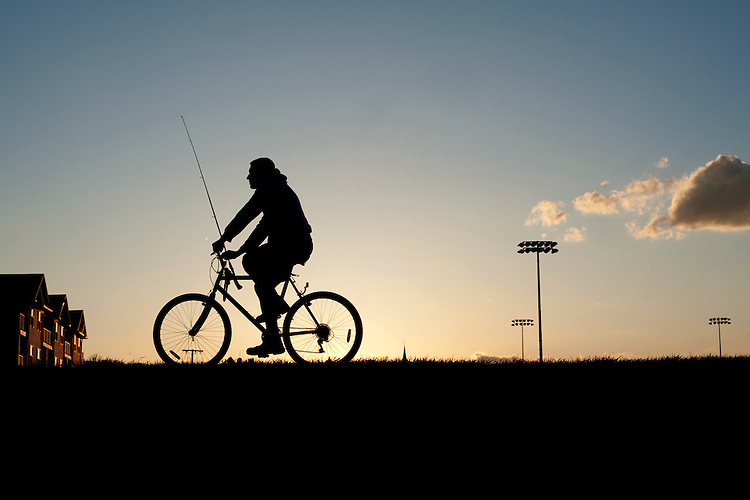 A man rides his bike on the bike path after returning from fishing. Photo by Ross Brinkerhoff