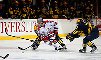 OSU Nick Schilkey brings the puck up the ice against Michigan defenders at Value City Arena in Columbus Dec. 2, 2013.