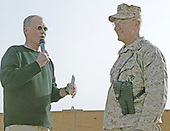 """David Letterman chats with Brigadier  General Richard S. Kramlich, 1st Force Service Support Group's commanding general, on stage during """"The Late Show"""" at Camp Taqaddum, Iraq, December 24, 2004. Letterman, along with his musical director Paul Shaffer and stage manager Biff Henderson, brought the popular late night television show to the Marines, sailors and soldiers currently stationed at Camp Taqaddum, Iraq. They were followed with a performance from """"Off the Wall,"""" a southern California band, which added to the holiday festivities. .Mandatory Credit: Luis R. Agostini / USMC via CNP."""
