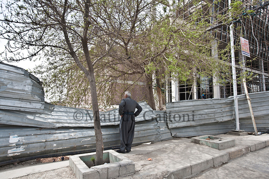 Iraq - Kurdistan - Sulaymaniyah -  A man looking at a construction site in Salem street