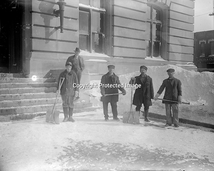 SNOW SHOVELERS AT THE POST OFFICE. John Johnson was listed in city directories as a laborer or janitor at the post office on and off from 1904 to 1917. When he resigned in 1917, his pay was $600 per year. He often photographed his workmates, here taking a break from shoveling a deep snowfall. They stand outside the south entrance, which was in-filled with a window in the remodeling and extension of 1914-1916.<br />