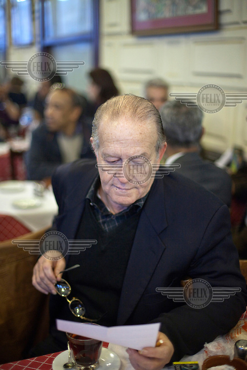 A journalist reads a letter in the crowded Cafe Riche. /Felix Features