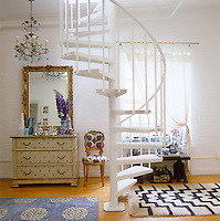 The spiral staircase is flanked by an antique chest of drawers, a gilded mirror and a chair