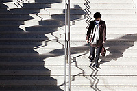 A salaryman wearing a scarf and a face mask goes down some steps at Tokyo Station, Tokyo, Japan. Friday, January 10th 2014