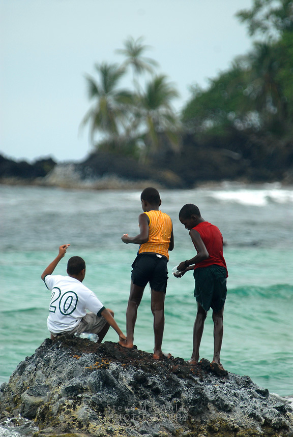Three young boys fishing from the rocks Bocas Del Toro, Panama