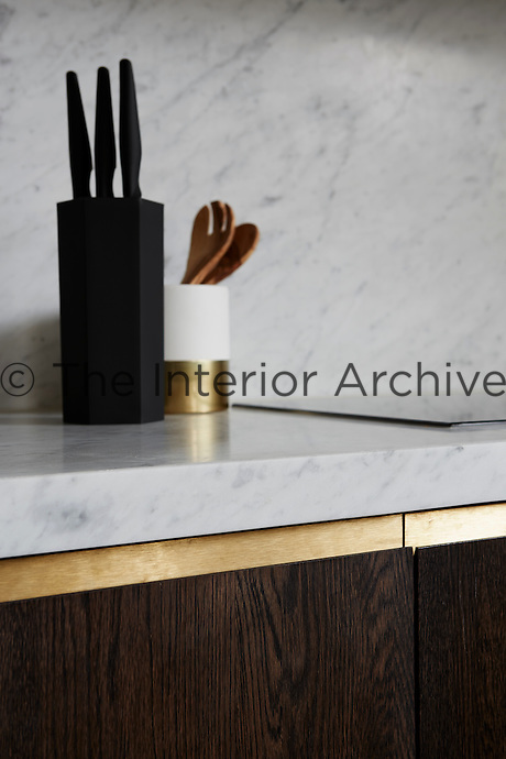 The bespoke joinery in the kitchen is subtle and unfussy and the dark wood is set off by the light grey marble.