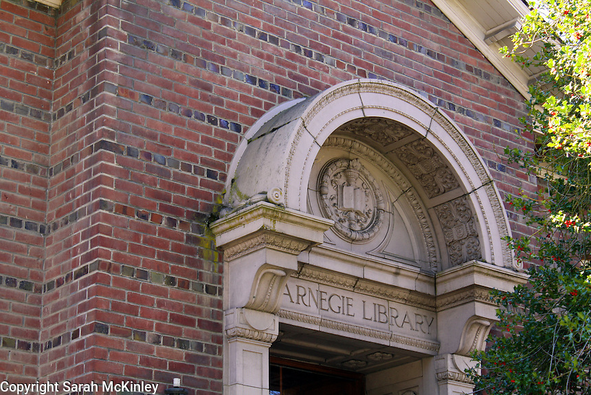 The ornately carved marble tympanum of the relieving arch over the doorway to the brick Carnegie Library in Willits in Mendocino County in Northern California.