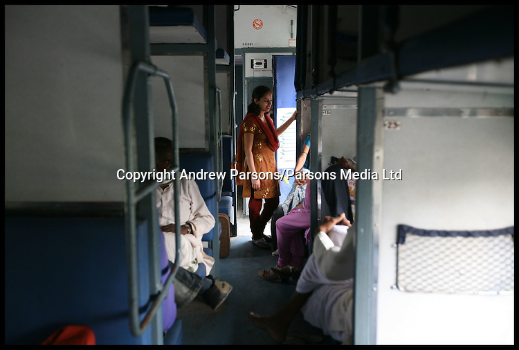 An Indian girl chats with friends in economy class of a Indian train  while traveling from Agra to Delhi, India. Photo By Andrew Parsons/Parsons Media Ltd info@parsonsmedia.net