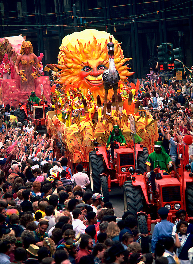 The sun float in the Rex parade at Mardi Gras with onlooking crowds. New Orleans, Louisiana.